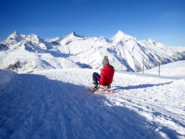 Girl in the Swiss mountains on Sledge - Taffpixture/shutterstock