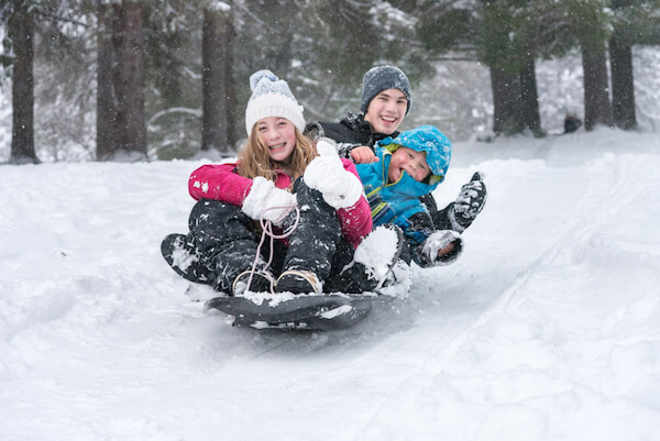 Kids tobogganing in snow