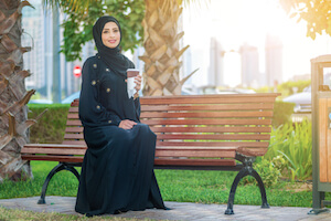 Smiling Arab woman dressed in an abaya sitting on a bench in sunshine - image by shutterstock.com