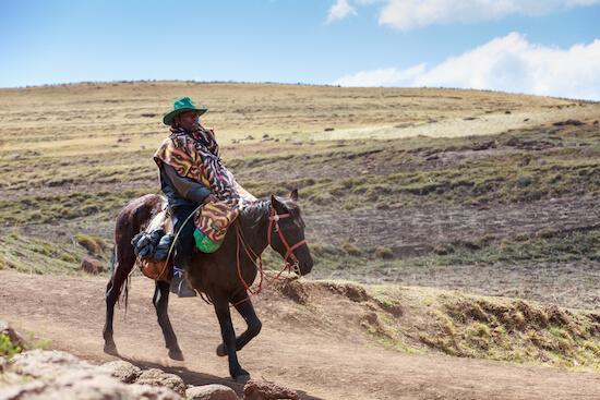 Basotho man dressed in typical Basotho blanket on horse - image by GilK/shutterstock.com