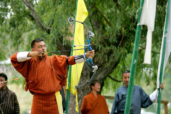 Bhutanese man in archery games - image by Oksana Perkins