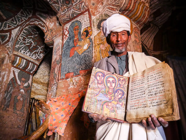 Man holding ancient Ethiopian gospel book from 5th century - image by Kanokwann/shutterstock.com