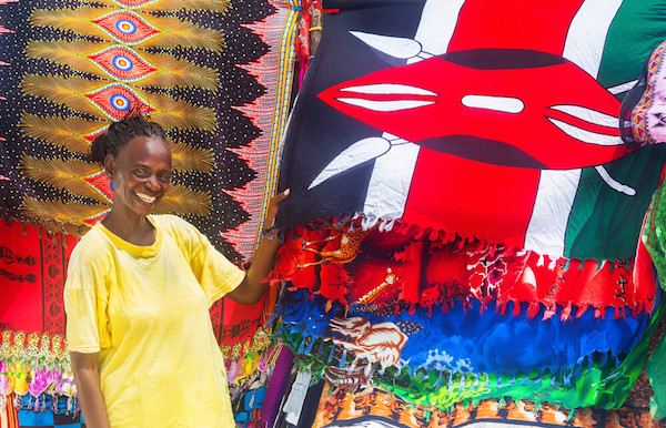Smiling Kenyan woman with flag: MarKord / Shutterstock.com