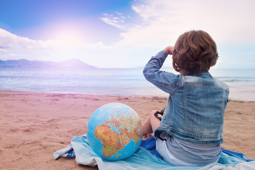 girl with globe looking across the sea - kids world travel guide