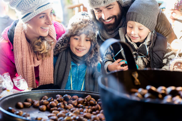 Family with two children holding maroni chestnuts at christmas market - image by shutterstock