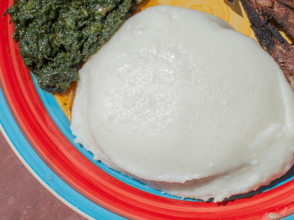 South African mieliepap on plate with morogo spinach and piece of meat