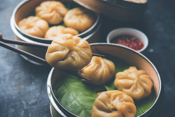 Nepalese momos with achar sauce in bowl with chopsticks