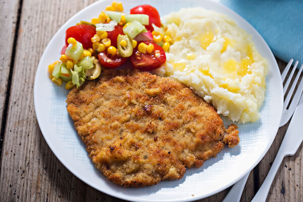 Polish schabowy is breaded cutlet or port chops served with potato mash and salad