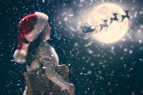 Girl looking at Santa and reindeers in snowy sky