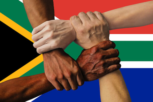 Multicultural South Africa - hands of different skin colour in front of South African flag