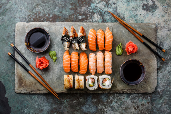 Sushi platter with wasabi, pickled ginger roses and chopsticks
