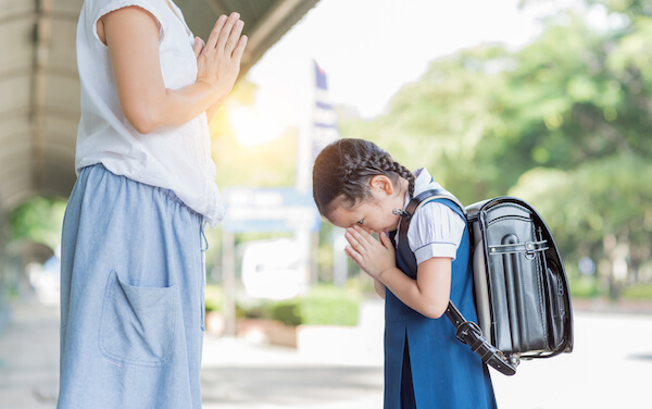 Thai child greeting the mother before going to school