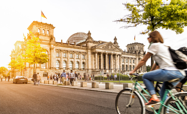 Germany Reichstag in Berlin with flag and cyclist