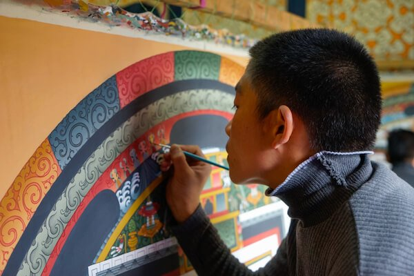 Young man refreshes the paint in a Bhutanese temple - image by Angela Maier/shutterstock.com