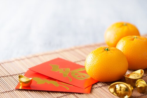 Chinese New Year red packets and oranges - image: shurtterstock.com