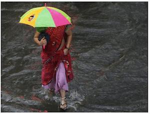 Indian woman walking through water - Flooding in India  - dpa