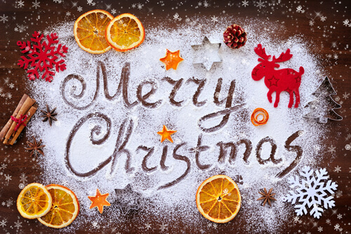 Merry Christmas food theme - written in icing sugar with orange slices and cinnamon sticks