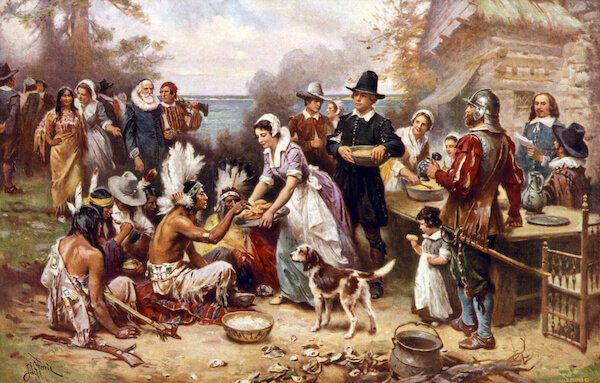 The first Thanksgiving, 1621, Pilgrims and natives gather to share a meal, oil painting by Jean Louis Gerome Ferris, 1932. - image by Everett Historical/shutterstock.com